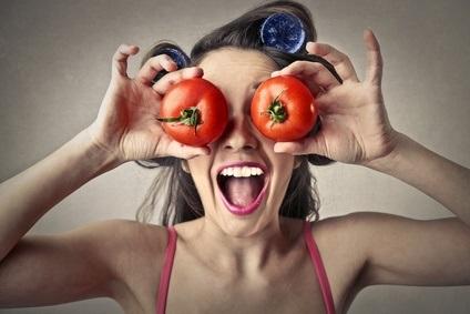 Vitamine - junge Frau hält sich Tomaten vor die Augen
