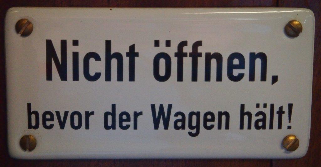 """Plus auf der Waage - Schild mit der Aufschrift """"Nicht öffnen, bevor der Wagen hält!"""""""