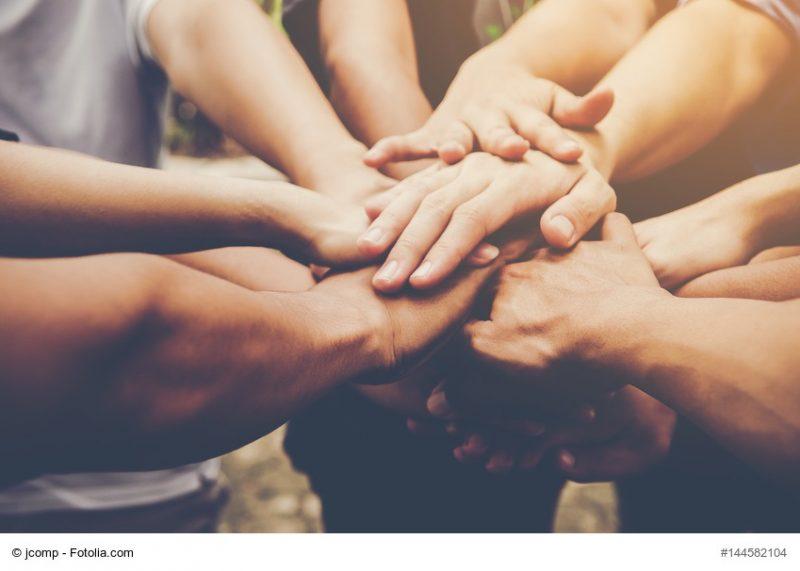 ein starker Zusammenhalt im LCHF Kurs - Hände vieler Menschen liegen aufeinander - Zeichen des Gruppengefühls